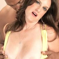 Old lady Gillian Sloan flashes her shaven fuckbox on the lap of youthfull ebony man
