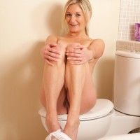 Elder light-haired solo model stripping naked to pose naked in the bathroom