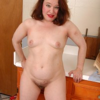 Older redhead mistress removing translucent outfit and lingerie to pose nude in kitchen