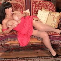 Plumper solo model Arianna Sinn lets her giant titties free from a dress in tan hosiery