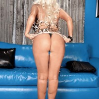 Gawky platinum-blonde MILF Brittany O'Neil uncovering massive boobies for ebony boy on leather chesterfield
