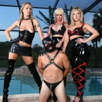 THREE uber-sexy chicks in latex garbs and stilettos debase hooded male submissive by pool