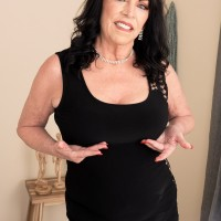 60 plus MILF Christina Starr seduces a youthfull guy while going bare-breasted in a ebony dress