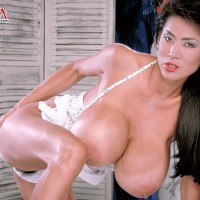 Oriental solo model Minka unsheathes her bush with her immense boobies on demonstrate on a bed