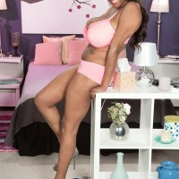 Ebony MILF Rachel Raxxx undressing down to matching pinkish brassiere and panty set on bed