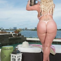 Blond BIG SEXY WOMAN Holly Wood struts about in a thong swimsuit next to the ocean