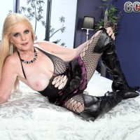 Blond grannie Charlie looses her enormous boobies in over the knee boots and fishnet body-stocking