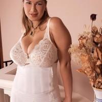 Sandy-haired MILF Terry Nova unleashing massive boobs from underneath melon-holder in milky lingerie