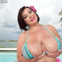 Black-haired MILF Paige Turner massaging huge swimsuit coated tits outdoors on beach