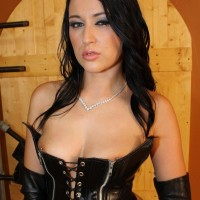 Brunette Dominant Ashley strutting about dungeon partly naked in fetish garb
