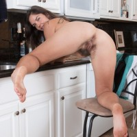 Euro first-timer Katie Z demonstrating furry underarms and natural thicket in kitchen
