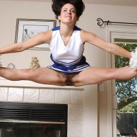 Pliable female doffs a cheerleader uniform before playing with her coochie while naked