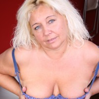 Elder sandy-haired BIG SEXY WOMAN undressing out of micro-skirt and lingerie to pose over weight rump in the nude