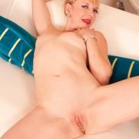 Elderly platinum-blonde doffs a black sundress and g-string to make her nude debut on a futon