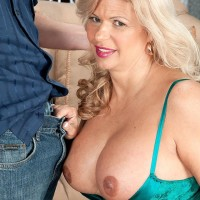 Older yellow-haired doll Miss Deb unveils her monster-sized boobies from her lingerie on a sofa