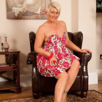 Aged platinum light-haired reveals her small breasts as she strips to stilettos on a leather chair