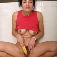 Aged dame strips nude in the kitchen before taking a banana to her furry pussy