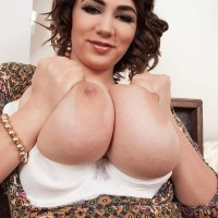 MILF solo model Alexya baring humungous titties from boulder-holder in tan pantyhose and high-heels