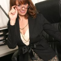 Nasty senior boss woman undressing down to pantyhose and high heeled shoes in her work environment