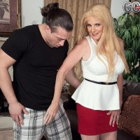 Older blond doll Charlie has her massive tits revealed by junior guy in a red microskirt