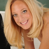 Older golden-haired MILF doffing biz clothes and lingerie to model nude