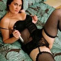 Experienced dark-haired woman in ebony hose inserting sex toy into shaven snatch in high heeled shoes