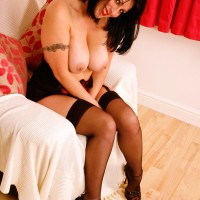 Elderly dark haired solo model revealing enormous titties and plus sized bum in black nylons and pumps