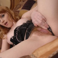 Red-haired solo chick with nice boobs stretches the lips of her wooly coochie on her bed