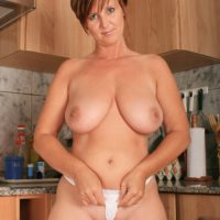 Aged housewife with short crimson hair releases her giant naturals for her first nude poses