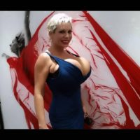 Golden-haired solo model Claudia Marie deep-throats on a nip after baring her large breasts