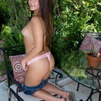 Eighteen yr old brown-haired Natalie Monroe strips to g-string panties on the patio in solo act