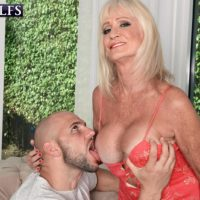 60 plus MILF Leah L'Amour entices a junior guy at the door with her enormous boobies out
