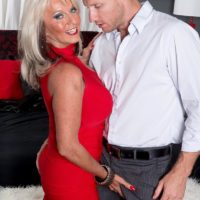 Aged adult movie starlet Sally D'Angelo flaunting superb legs and exposing massive titties
