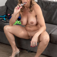 Big-boobed older blonde Kenzi Foxx models bikinis before anal sex on a couch with a stud