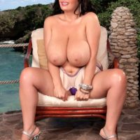 Monster-sized titted dark-haired Arianna Sinn plays with her swell nipples after getting naked on a patio