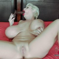 Monster-sized breasted platinum blond Claudia Marie gargles on a faux-cock while masturbating on a bed