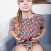 Platinum-blonde first timer Jamaica finger parts her bush during a naked solo shoot on a chesterfield