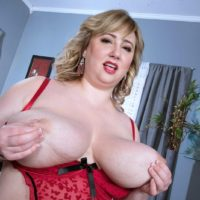 Ash-blonde BIG SEXY WOMAN solo model Laddie Lynn letting huge saggy tits loose from lingerie
