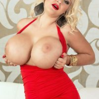 Blond MILF Dolly Fox letting massive boobies free from crimson dress in high-heels