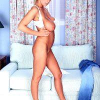 Fair-haired MILF XXX film star Autumn Jade revealing enormous boobs while peeling off denim jeans