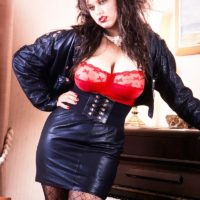 Dark-haired solo model Jeannine Oldfield unleashes her large titties in leather and pantyhose
