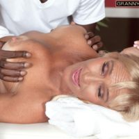 Busty platinum-blonde granny Brittney Snow has her titties played with by her ebony massagist