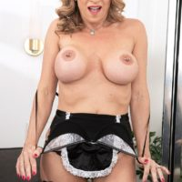 Big-titted senior maid Kenzi Foxx munches a nipple while getting nude for faux penis slurping