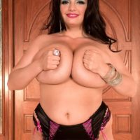 Curvaceous brunette MILF Arianna Sinn letting huge breasts loose from brassiere in nylons