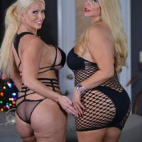 Curvy elderly blond Karen Fisher and her lezzy gf break out a sex toy on a bed