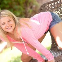 Adorable blond teen Mindy uncovers her stiff tits and g-string garbed booty on a patio