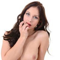 Enticing brunette model Ann O Fee finger fucks her honeypot after taking off her crimson swimsuit