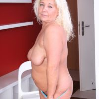 Experienced sandy-haired gal discards a mini-skirt and brassiere before sliding underwear over her enormous arse