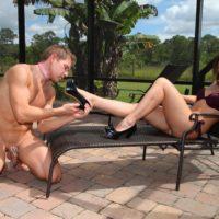 High heeled and bikini clad Dominatrix Callie Calypso receiving foot worship from a male sub