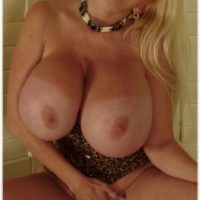 Experienced blonde dame Kayla Kleevage sets her enlargened boobies and bush free on a futon